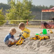 children playing in the sand with trucks at acton quarry
